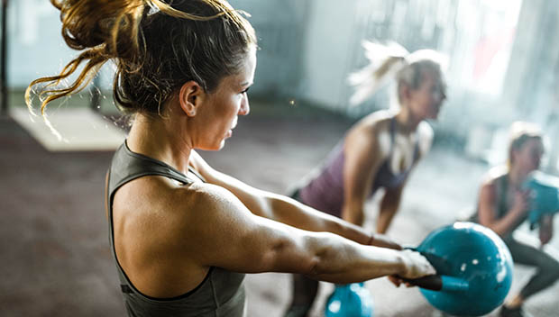 Determined athletic woman having gym training with kettle bell in a gym. Her friends are in the background.